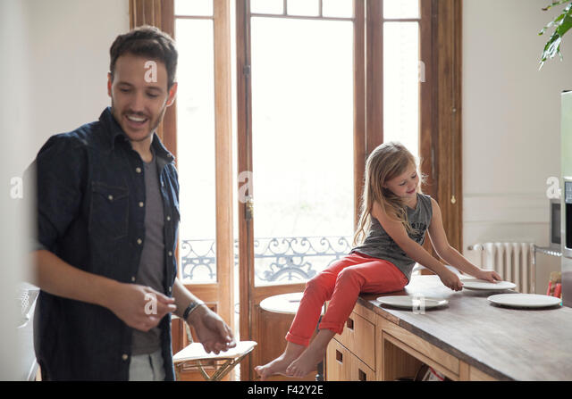 Girl helping father set table for family meal - Stock-Bilder