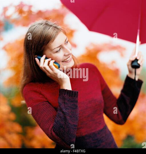 autumn cell phone color image communication outdoors rain smiling umbrella weather woman - Stock-Bilder