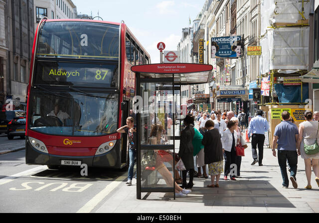 the-strand-london-uk-busy-with-visitors-red-bus-at-bus-stop-number-e50beh.jpg