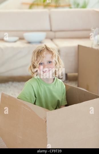 Boy hiding in cardboard box - Stock Image
