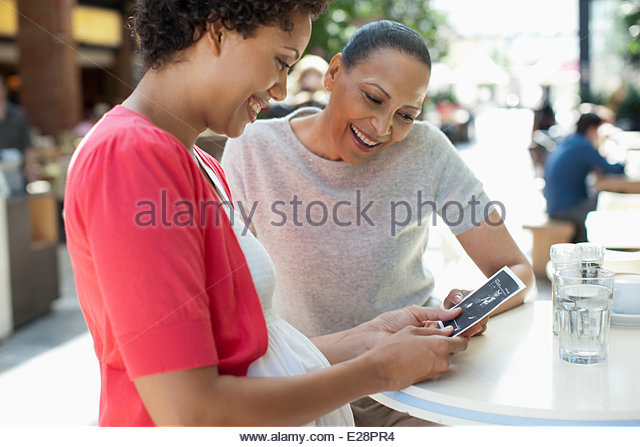 Friends looking at pregnancy sonogram image - Stock-Bilder