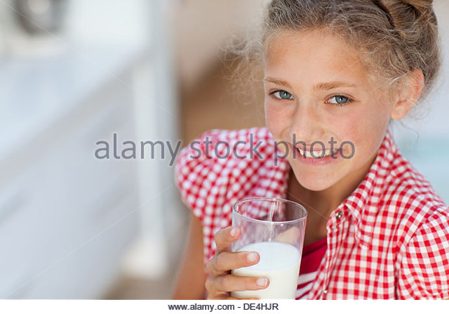 Smiling girl with milk mustache holding glass of milk - Stock Image