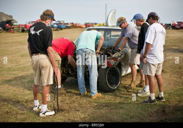Mechanics piece together the remains of their Demolition Derby car so that it can still compete. - Stock Image