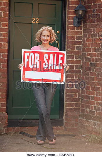 A mature woman holding a property for sale sign - Stock Image