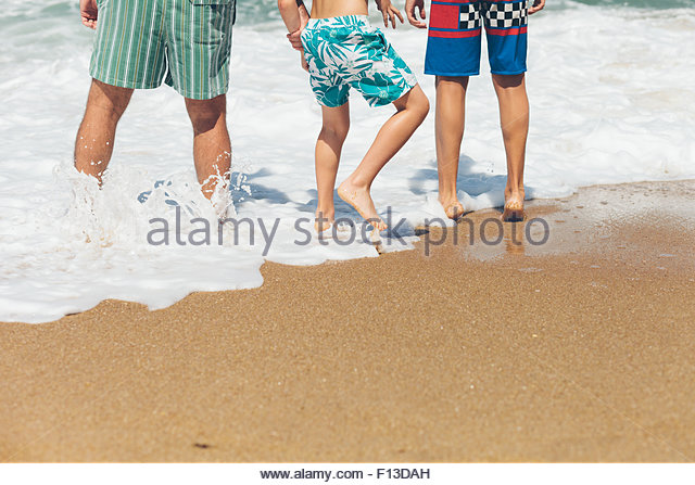 Waist down view of three people  standing in the surf at the beach - Stock Image
