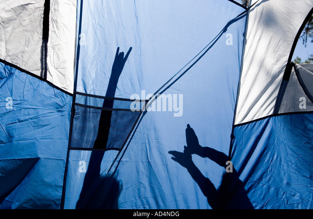 Children making shadow puppets behind a tent - Stock-Bilder