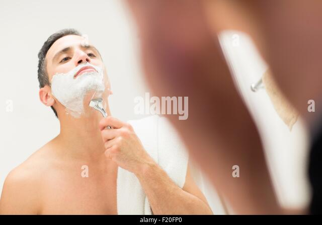 Mid adult man, looking in mirror, shaving - Stock Image