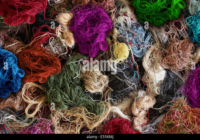 Textile industry background as a group of multi colored entangled sewing threads as a symbol for the fashion industry - Stock Image