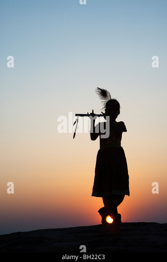 Silhouette of an Indian girl pretending to be Lord krishna at sunset. Andhra Pradesh, India - Stock Image
