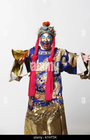Portrait of a male Chinese opera performer holding a bowl full of gold coins - Stock Image