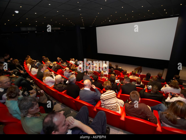 people watching a cinema screen in a theatre - Stock Image