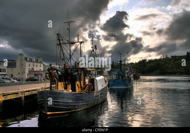 Traditional fishing boats and a dramatic sky in Stornoway harbour, Western Isles, Scotland, United Kingdom - Stock Image