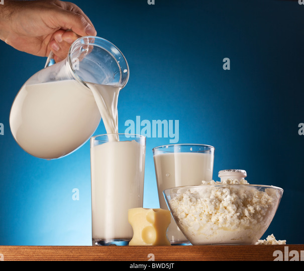 Milk products. Man hand is pouring milk from jar into glass. - Stock Image