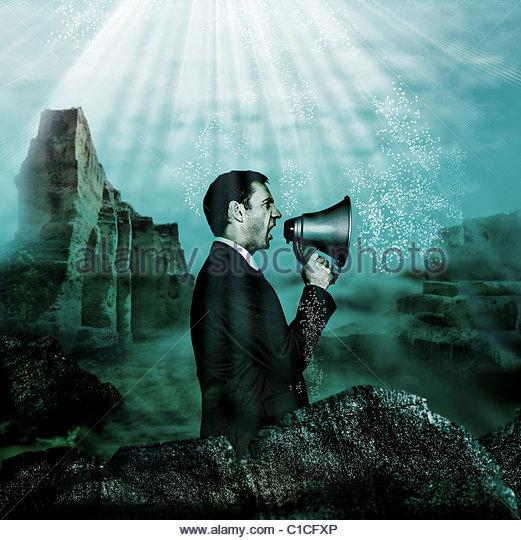 Businessman holding megaphone under water - Stock-Bilder