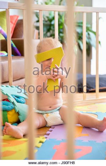 Smiling Baby Boy In Wooden Playpen At Home - Stock-Bilder