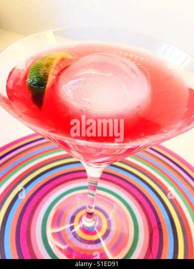 A cosmopolitan cocktail in a martini glass on a glass bull's-eye, USA - Stock Image