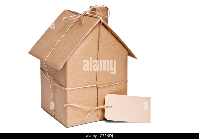 Photo of a wrapped house in brown recycled paper with label, cut out on a white background. - Stock Image