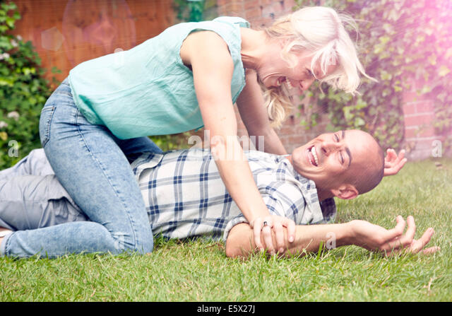 Happy couple play fighting in garden - Stock Image