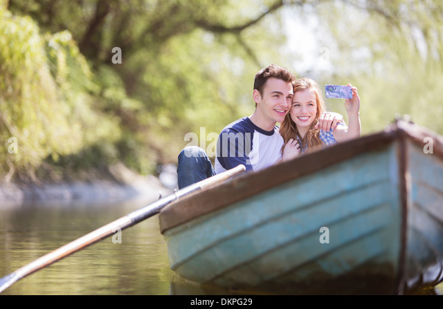 Couple taking self-portraits in rowboat - Stock Image