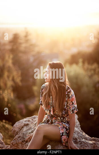 Mixed race woman sitting on boulder - Stock Image