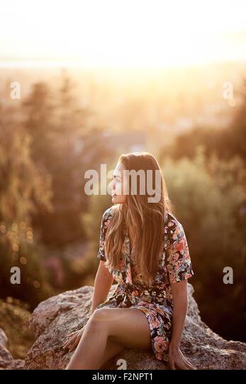 Mixed race woman sitting on boulder - Stock-Bilder