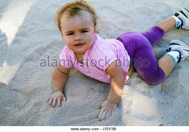 Miami Beach Florida Lummus Park baby girl crawling sand on face stuck to playing dirt bacteria health - Stock Image