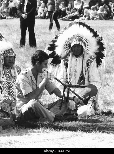 Prince Charles attending a Blackfoot Indian ceremony at Calgary Canada July 1977 Puffing a peace pipe watched by - Stock Image