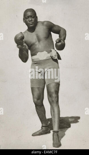 Jack Johnson, full-length portrait, standing facing front, wearing boxing shorts and boxing gloves, circa 1910 - Stock Image