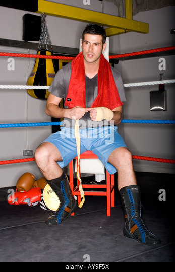 Boxer taping hands in boxing ring - Stock Image