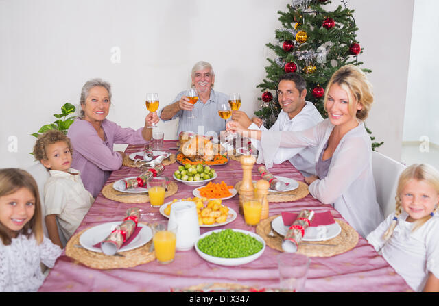 Family raising their glasses at christmas - Stock Image