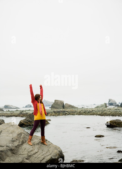 woman raising her arms in the air on a rock overlooking a craggy coastline of the ocean - Stock-Bilder