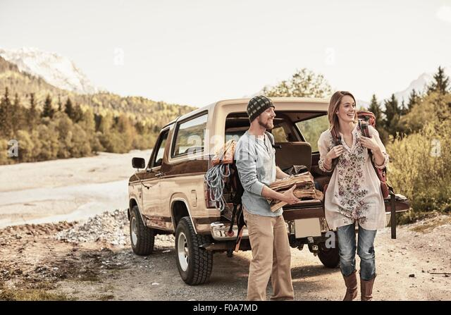 Young couple preparing to go hiking, carrying firewood - Stock-Bilder
