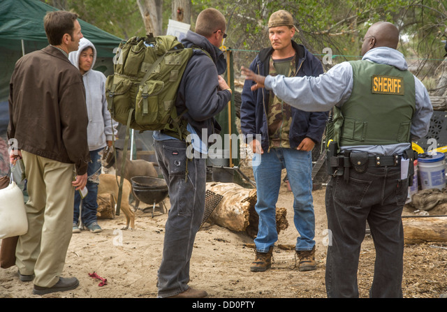 A minister and a sheriff's deputy meet a homeless couple and their dogs living in a home-made shack - Stock Image