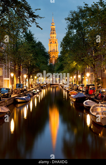 The Zuiderkerk illuminated at night and reflected in a canal lined with trees. Amsterdam, The Netherlands - Stock Image