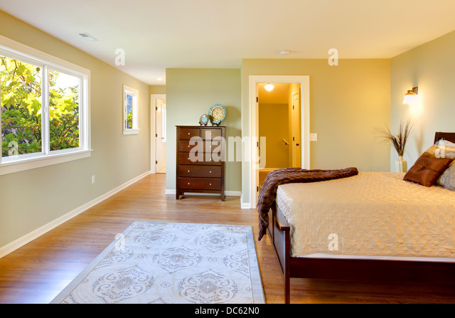 Large bedroom with modern brown bed and green walls. - Stock Image