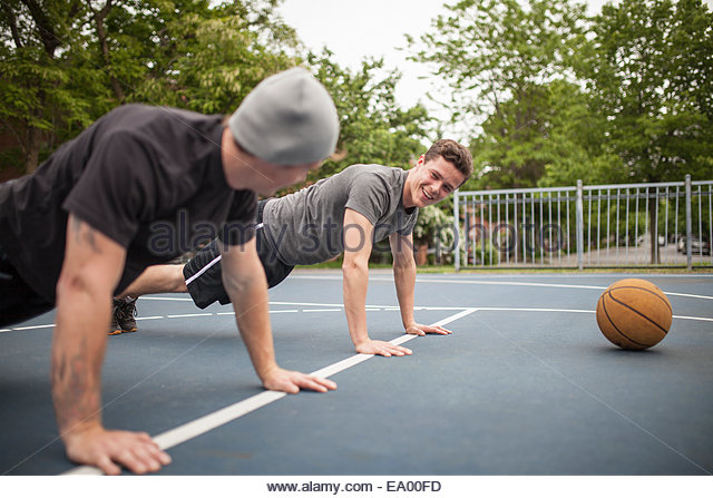 Young men doing push ups on basketball court - Stock Image