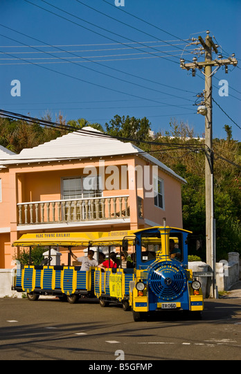 Bermuda St Georges yellow tour train pink house with bright colors - Stock Image