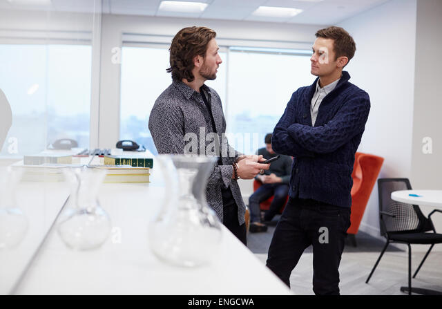 Two men in an office, standing and talking, one with his arms folded. - Stock Image