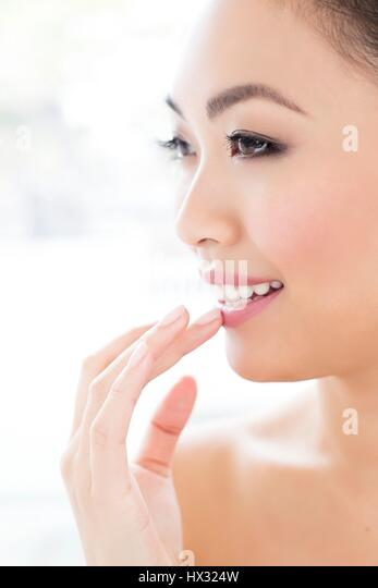 MODEL RELEASED. Young Asian woman touching lip, portrait. - Stock-Bilder