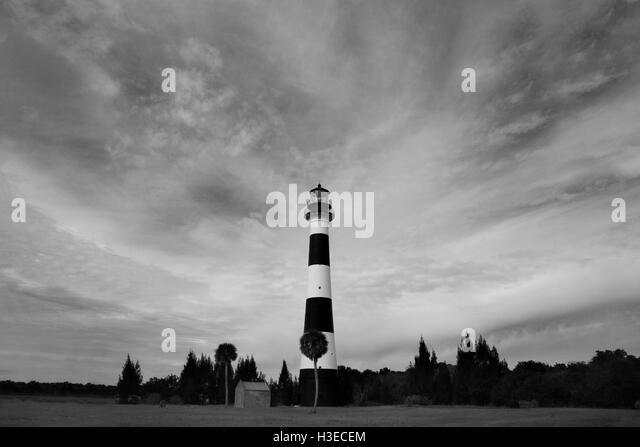 Distinctive Cape Canaveral Lighthouse in a black & white image with rises into sweeping clouds above the cape. - Stock Image
