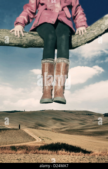 a girl sitting on a branch high over a field - Stock Image