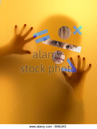 A boy peers through a screen covered in mathematics symbols - Stock Image