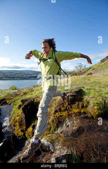 Man jumps across a waterfall while hiking. - Stock Image