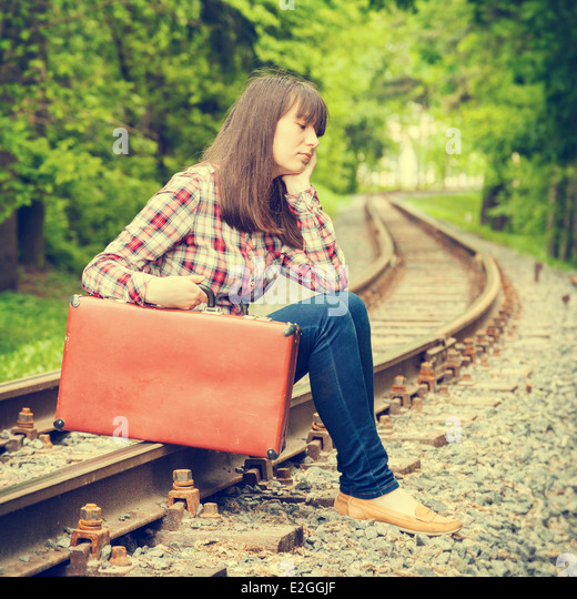 young teenager sad girl with suitcase sitting on the rails - Stock Image