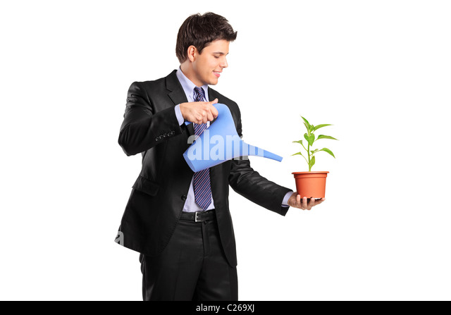 Portrait of a businessman holding a flower and watering can - Stock Image