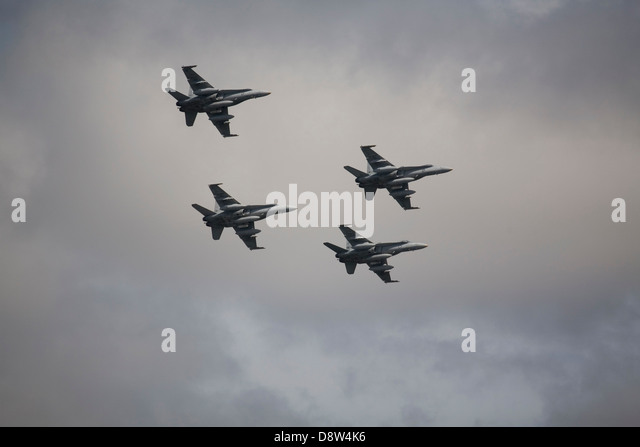 Four F/A-18 Hornet jet fighter aircraft of the Royal Australian Airforce flying in formation against grey sky - Stock Image