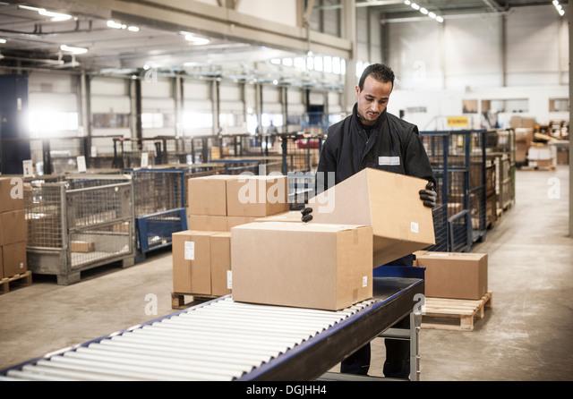 Male warehouse worker checking cardboard box from conveyor belt - Stock-Bilder