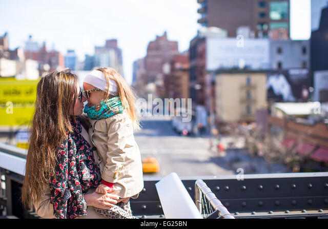 Adorable little girl and mother enjoy sunny day on New York's High Line - Stock Image
