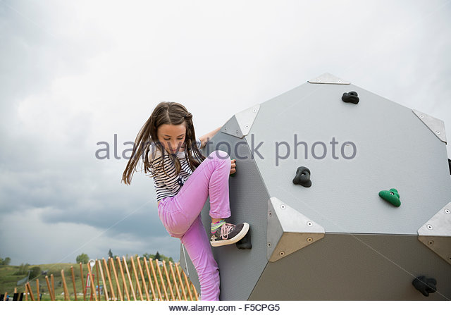 Girl climbing geometric shape at playground - Stock Image