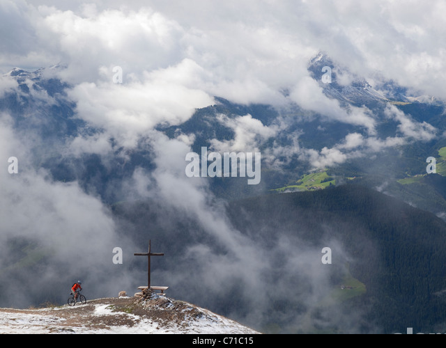 A mountain biker arrives at a cross on the summit of Kronplatz, mountains and clouds in the background. - Stock Image